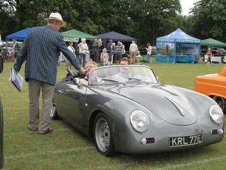 Andrew Snowdon speaks to the owner of a 356 Porsche Replica from the motorcade of classic cars
